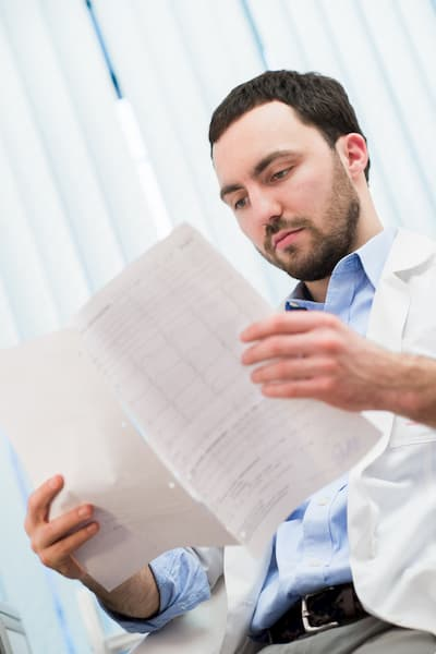 DOT physical exam requirements Sunshine Urgent Care | Doctor looking at paperwork